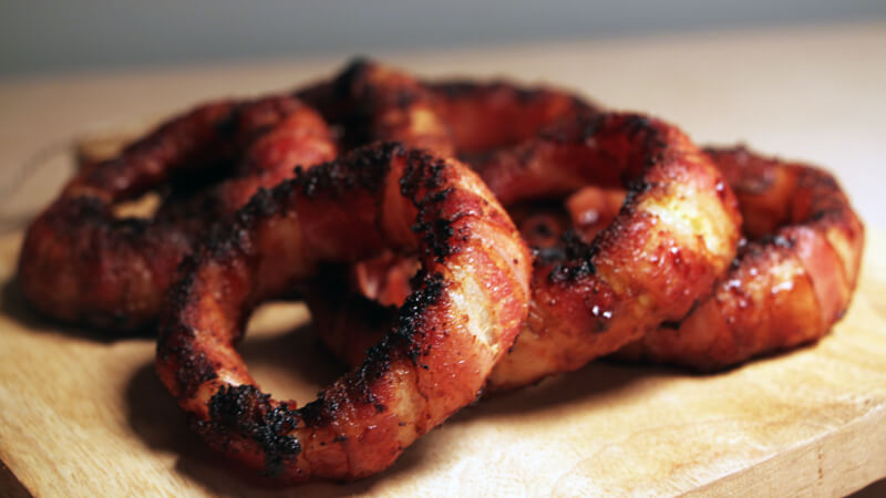 Deze in bacon gewikkelde uienringen bevatten alle BBQ smaken die je maar kunt wensen!